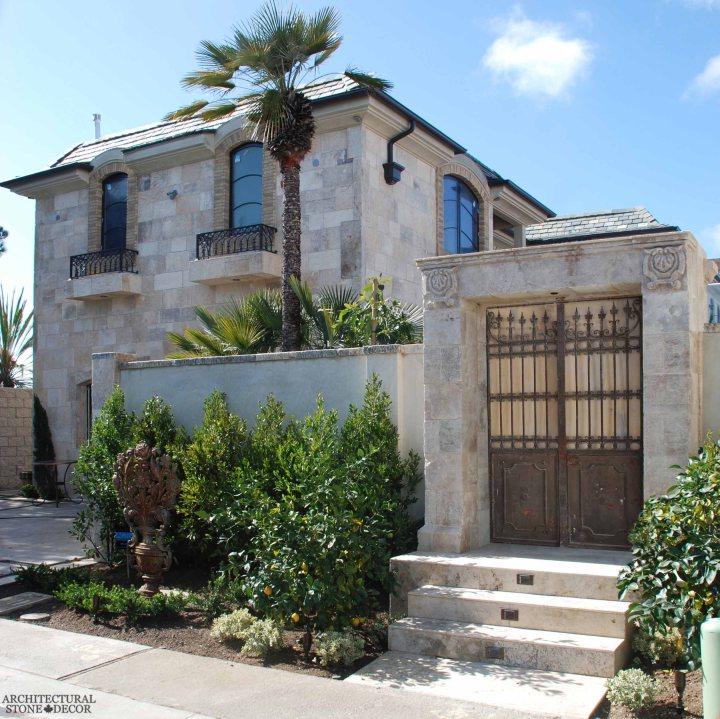 Coastal Mediterranean style villa home old world limestone entryway wall cladding wrought iron metal gate Canada Toronto