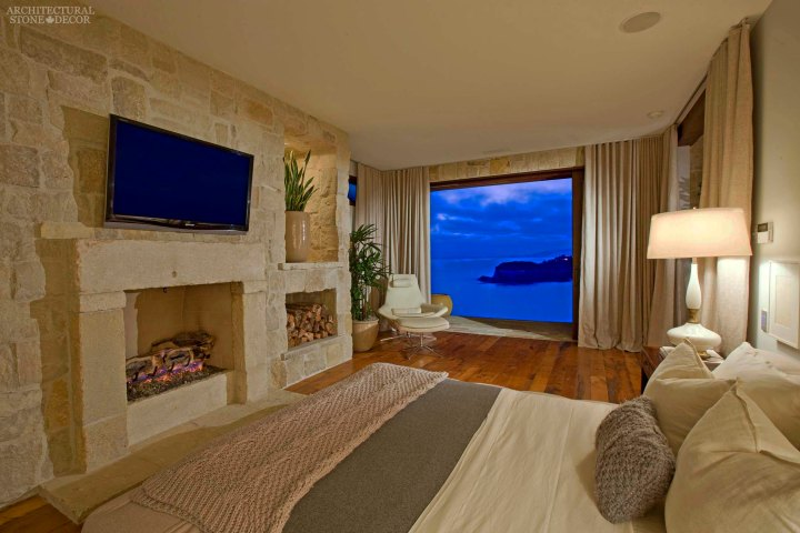 west coast style coastal mediterranean master bedroom reclaimed antiqued limestone hand carved fireplace mantel cladding Canada ca