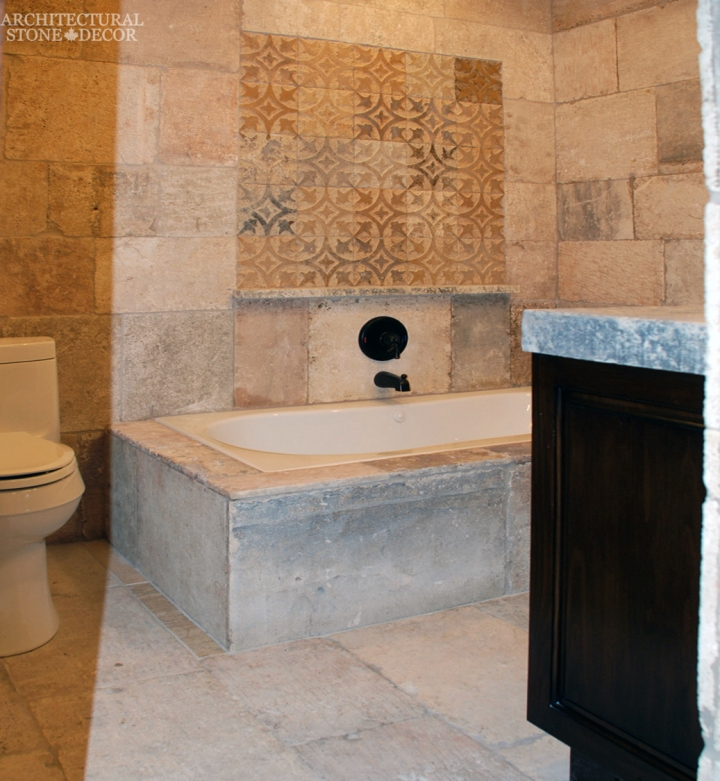 Tuscan style master bathroom reclaimed limestone flooring wall cladding bath tub canada ca
